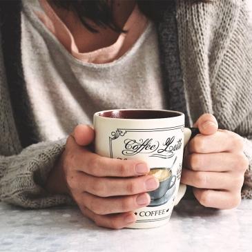 Ragazza che beve caffè in una tazza per colazione